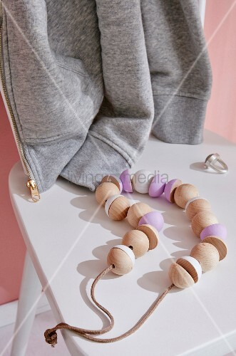 A homemade necklace of wooden beads strung on a leather cord on a white chair with a ring