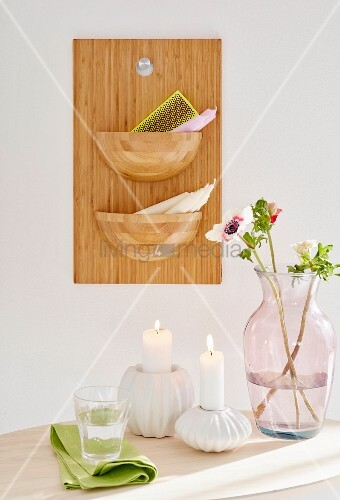 Burning candles in white candle holders and a glass vase in front of a homemade wooden board with bowl-shaped containers