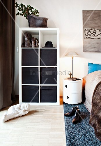 Black storage baskets in white shelving compartments in bedroom