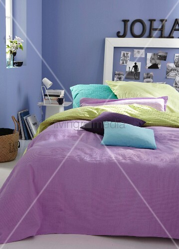 Colourful cushion covers on a bed with a purple plaid