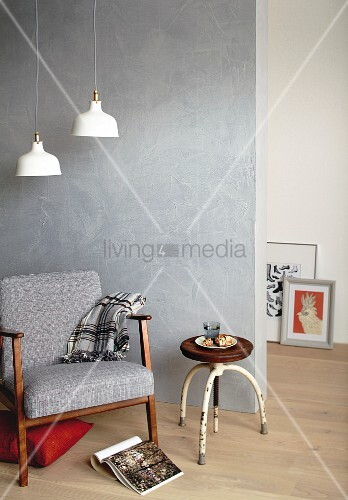Retro armchair and stool in front of concrete-effect wall