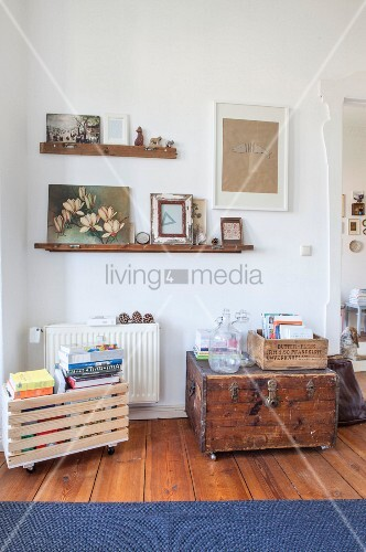 Wooden crate and trunk on castors below pictures on narrow shelves