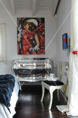 Silver chest of drawers with curved front and legs below modern painting