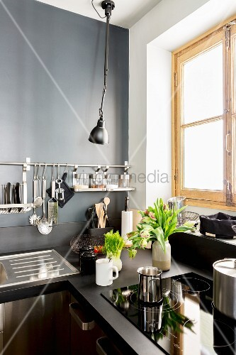 Dark kitchen with grey wall and utensils hung from wall-ounted bar