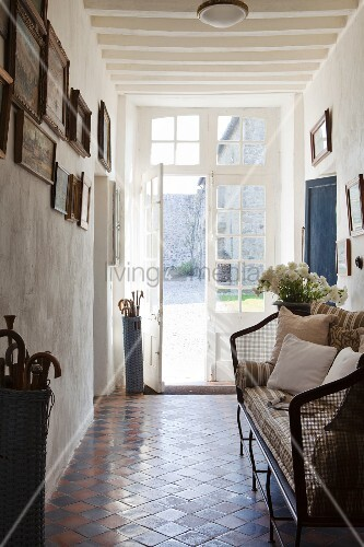 Terracotta floor tiles laid diagonally and vintage-style couch in hallway