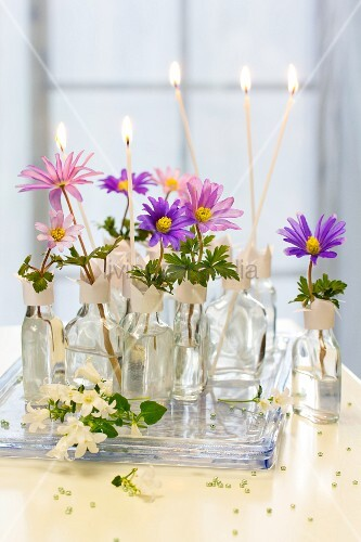 Spring flowers and candles in liqueur bottles used as vases with hand-made paper collars