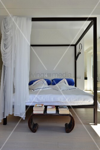 Oriental side table in front of black four-poster bed