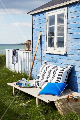 Camp bed outside blue beach hut