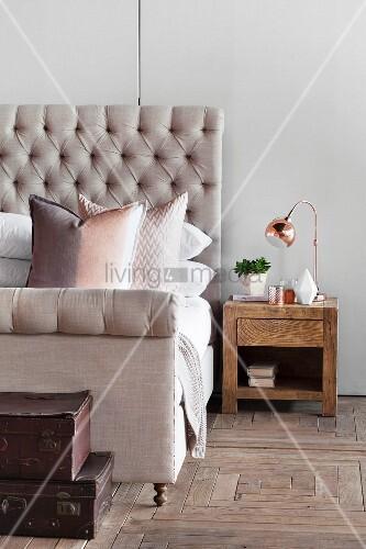 Bett mit gepolstertem Haupt und roséfarbenen Kissen, alte Koffer und ein Nachttisch aus Holz