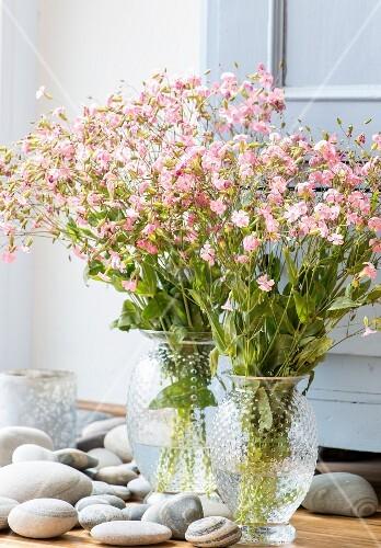 Blumenstrauss in Glasvasen zwischen Steinen auf Boden