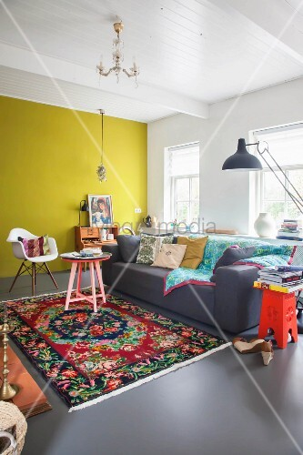 Multicoloured rug and yellow wall in colourful living room