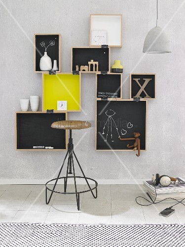Hand-made, wall-mounted shelving made from wooden crated and chalkboard paint