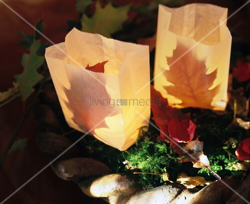 Paper-bag candles lanterns decorated with autumn leaves