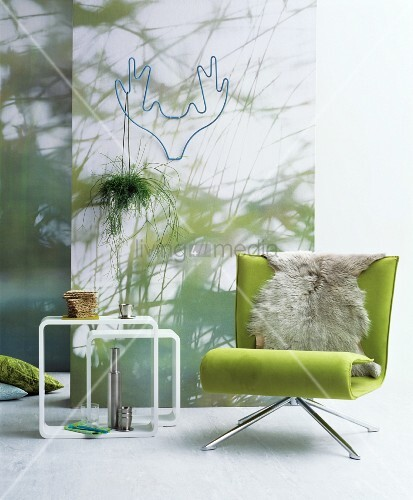 gr ner sessel mit fell vor einer wand mit fototapete bild kaufen living4media. Black Bedroom Furniture Sets. Home Design Ideas