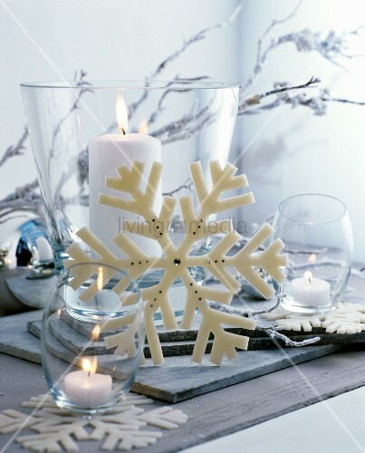 Christmas arrangement of white candles in various glass vessels and snowflake ornament