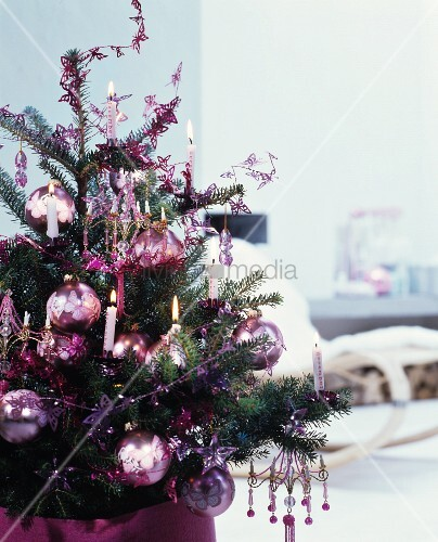 Christmas tree romantically decorated with shiny baubles and real candles
