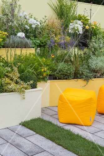 Terraced beds in shades of yellow in courtyard garden