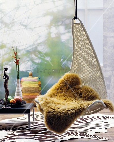 Fur blanket on hanging chair above zebra-skin rug amongst ethnic accessories