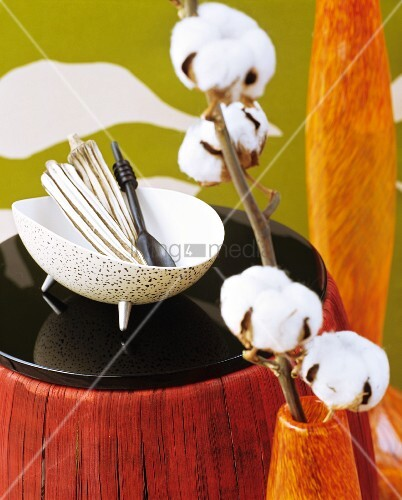 Baumwollzweig in einer Vase, Schale mit Ethno-Deko