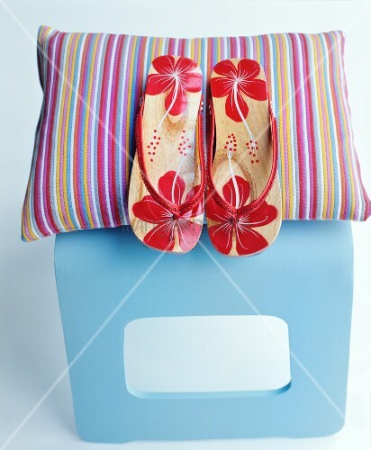 Flip-flops with red floral pattern and colourful striped cushion on pale blue stool