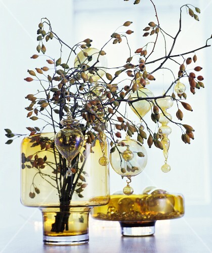 Branches of rose hips decorated with glass baubles in yellow glass vase