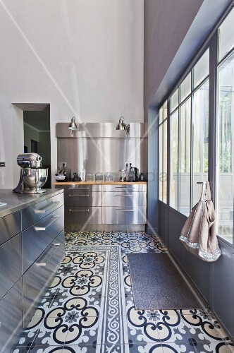 Modern stainless steel kitchen with cement-tiled floor and industrial windows