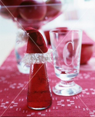 Bottle of Campari and soda decorated with Father Christmas hat on red table runner next to glass with etched initial