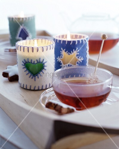 Tealight holders with felt covers and cup of tea with rock sugar swizzle stick