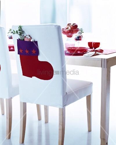 Felt Christmas stocking on backrest of white chair