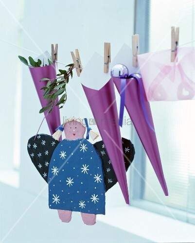 Advent calendar hand-made from purple cones hung from cord and hand-made angel figurine