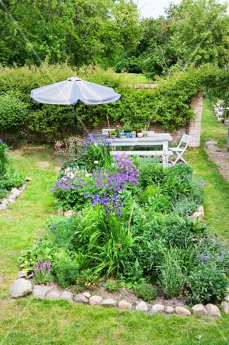 Flowerbeds edged with stones and seating area in summery garden