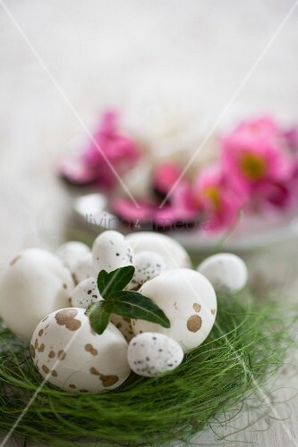 Speckled eggs of various sizes in nest