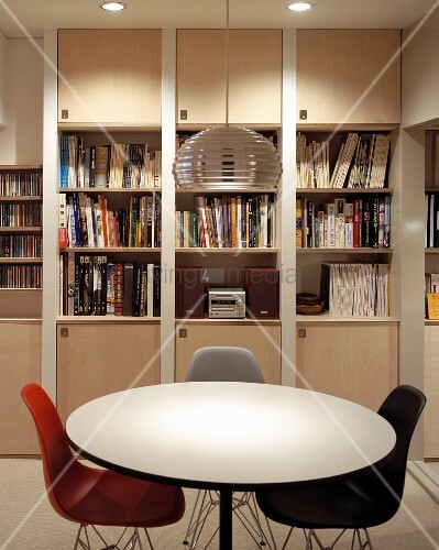 Round dining table and colored shell chairs in Bauhaus style in front of a built-in book shelf