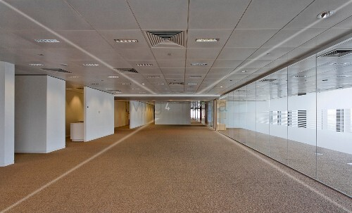 Reflective wall opposite white wall elements in wide corridor with coffer-style ceiling panels