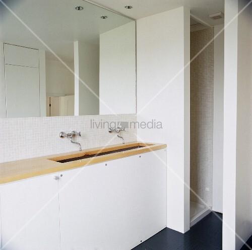 schlichtes weisses badezimmer mit heller holzplatte auf waschtisch vor vollfl chigem wandspiegel. Black Bedroom Furniture Sets. Home Design Ideas