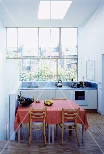 rosa tischdecke auf esstisch mit rustikalen st hlen in offener weisser k che bild kaufen. Black Bedroom Furniture Sets. Home Design Ideas