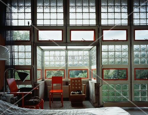 Industrial hall with glass brick wall and assorted chairs in the sleeping quarters