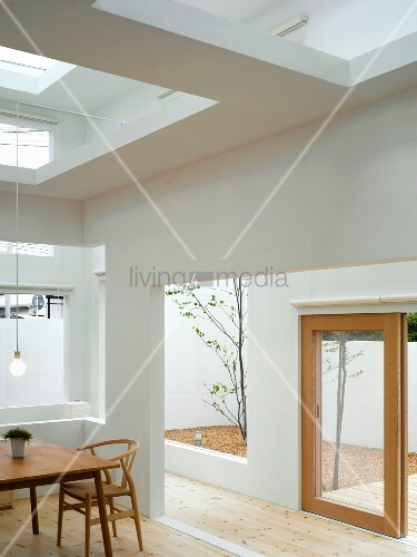 Simple chair made of light wood in Bauhaus style in a modern house with cut outs in the ceiling and wall with a view of courtyard