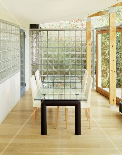 Glass top dining table and upholstered chairs in front of a glass brick wall