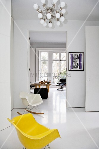 A yellow Bauhaus-style chair in a white, open-plan living room