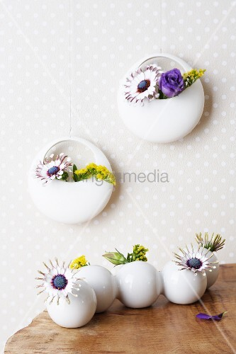 Goldenrod, blue daisies and lisianthus in round vases on a table and on a wall
