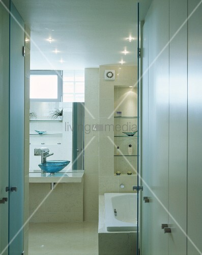 White built-in cupboards in front of an open bathroom door with a view of the bathtub and vanity