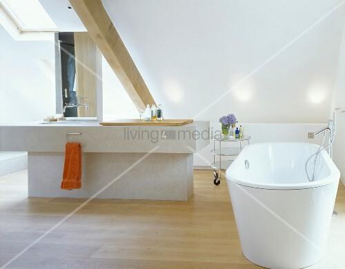 Freistehende Badewanne mit Designerstandarmatur und Sanitärinsel unter Dachschräge – Bild kaufen ...
