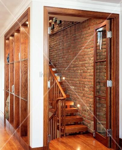 Vom wohnraum abgetrennter treppenraum mit glast r und holztreppe vor backsteinwand bild kaufen - Backsteinwand wohnzimmer ...