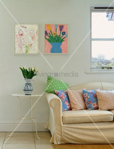 Light upholstered sofa with cushions in front of children's pictures on wall