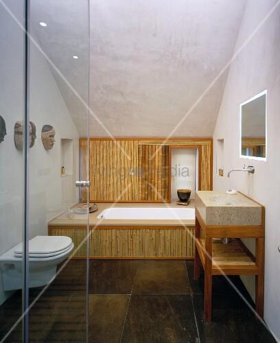 Blick Durch Offene Glastür In Modernes Bad Mit Bambusverkleidung An  Badewannenfront Und Braun Marmorierten Steinfliesen