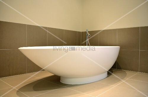 freistehende asymmetrische badewanne vor grossen fliesen in warmem grau bild kaufen. Black Bedroom Furniture Sets. Home Design Ideas