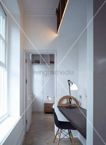 Simple office niche with desk lamp next to open door with view into bedroom