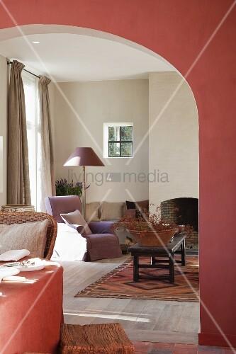 Lachsrote Wand im Esszimmer mit breitem Rundbogen und Blick in das Wohnzimmer auf offenen Kamin ...