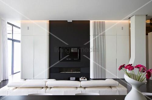 Designer Wohnzimmer   Weisse Faltwand Vor Schwarzer Einbaufront Mit Kamin  Und TV